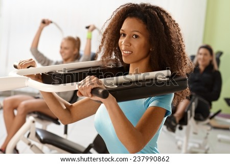 Pretty ethnic girl exercising on weight machine at the gym, smiling. - stock photo