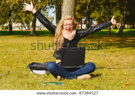 pretty excited girl with a laptop in the park - stock photo