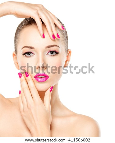 Pretty face of a beautiful  girl with pink eye makeup and bright pink  nails. Fashion model posing on white background - stock photo