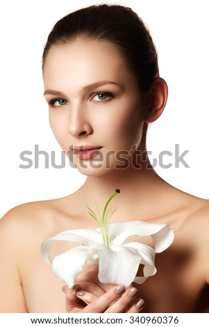 Pretty face of beautiful young woman with lily on hands - white background. Beauty face of young woman with flower. Beauty treatment concept