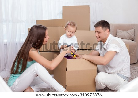 Pretty family is packing their staff with joy. A husband and wife are sitting on floor and helping their daughter to put some thing in a box. They are smiling - stock photo
