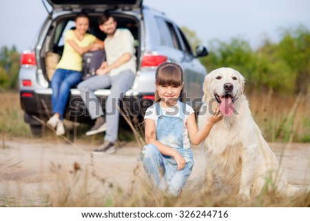 Pretty family is resting in the nature and smiling. The girl is kneeing and playing with dog. The man and woman are sitting on open car trunk. They are looking at daughter happily - stock photo