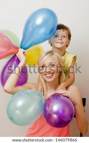 pretty family with color balloons on white background, blond woman with little boy on birthday party - stock photo