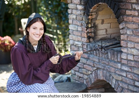 Pretty farm girl dressed in traditional clothing baking bread in an outdoors oven - stock photo