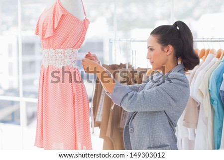 Pretty fashion designer measuring dress on a mannequin in a studio - stock photo