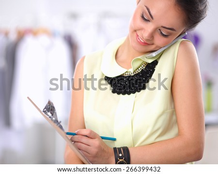 Pretty fashion designer working in office using mobile phone, isolated