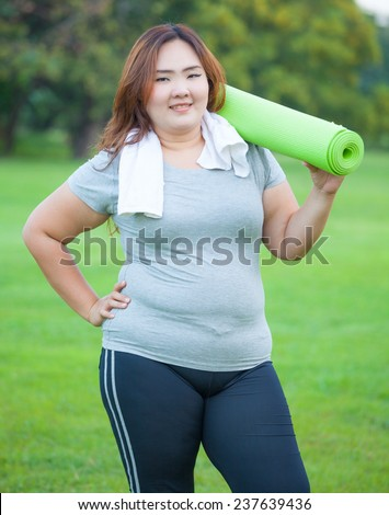 Pretty fat asian woman going to work out with her yoga mat - stock photo