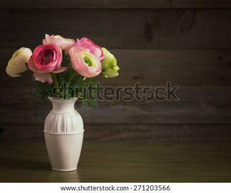 Pretty Faux Ranuncula Flower Bouquet in a White Vase in Rustic Wood Board Setting with room or space in  background for copy, text, your words.  Horizontal can be cropped to vertical.  Low key - stock photo