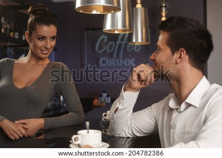 Pretty female bartender flirting with young man in bar, smiling.