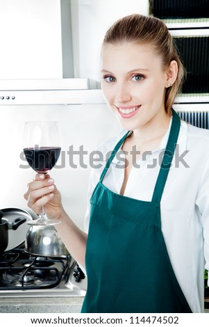 Pretty female blond woman in kitchen cooking with glass of red wine in hand