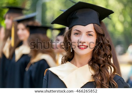 Pretty female college graduate at graduation with classmates