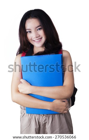 Pretty female college student holding a folder while smiling at the camera in the studio