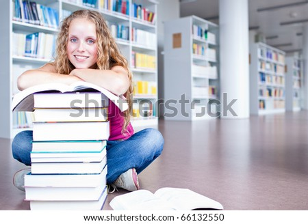 pretty female college student in a library (shallow DOF; color toned image) - stock photo