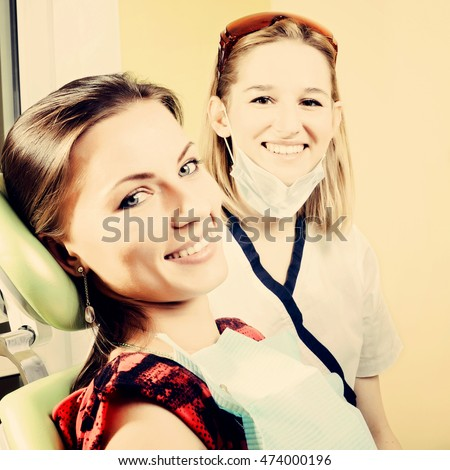 Pretty female dentist and female patient looking to camera in dental office, toned image
