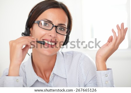Pretty female employee with spectacles talking on headphones while smiling and looking at you - stock photo