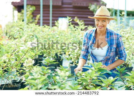 Pretty female farmer looking at camera in the garden - stock photo