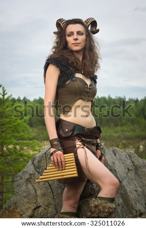 Pretty female faun in a wood. Woman with a mythological creature playing flute