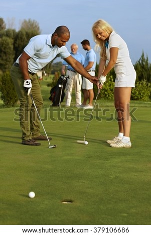 Pretty female golfer learning putting on the green. - stock photo