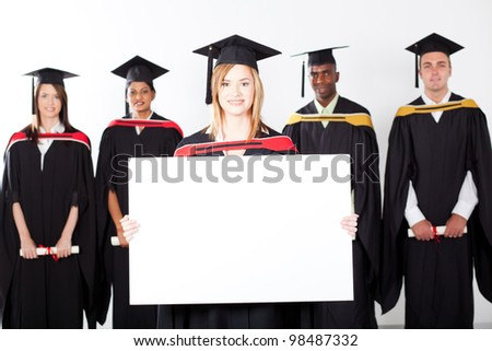 pretty female graduate holding white board with classmates in background - stock photo