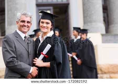 pretty female graduate with her father at university graduation - stock photo