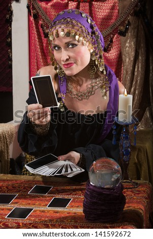 Pretty female gypsy fortune teller with tarot cards - stock photo
