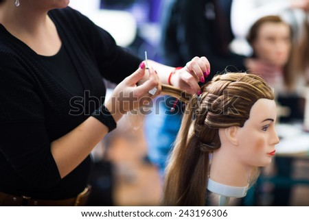 Pretty female hairdresser/haidressing apprentice/student training on an apprentice head - stock photo