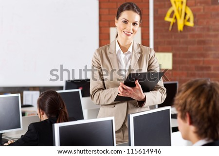 pretty female high school teacher portrait in computer room - stock photo