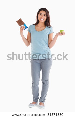 Pretty female holding a chocolate bar and an apple while standing against a white background