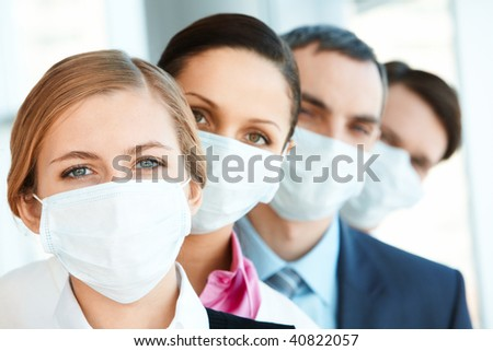 Pretty female in protective mask looking at camera with row of partners behind - stock photo