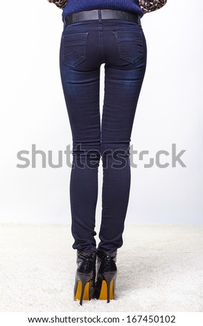 Pretty female legs in jeans and high heel shoes, back view