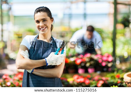 pretty female nursery worker portrait with pruner - stock photo