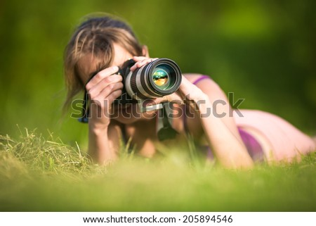 Pretty female photographer lying in grass, on a lovely summer day, taking pictures with her DSLR camera and a telephoto lens - stock photo