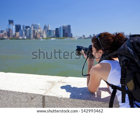 Pretty female photographer taking a picture of New York - stock photo