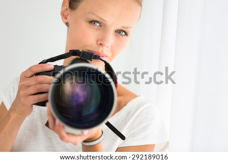 Pretty, female photographer with digital camera - DSLR and a huge telephoto lens (color toned image; shallow DOF) - stock photo