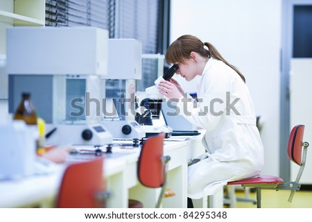 pretty female researcher using a microscope in a lab - stock photo
