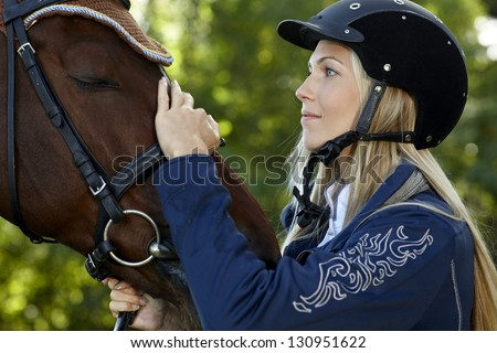 Pretty female rider caressing horse forehead with love. - stock photo