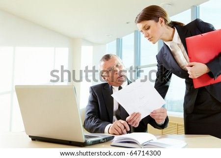 Pretty female showing document to her boss in the office - stock photo