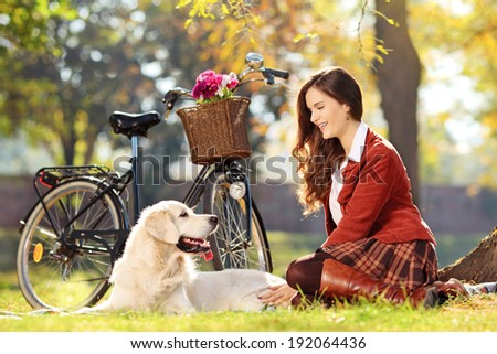 Pretty female sitting down with her dog in a park - stock photo