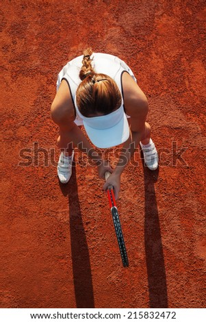 Pretty Female Tennis Player Is Prepared To Hit Tennis Ball. View From Above. - stock photo