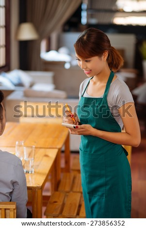 Pretty female waiter in apron taking an order - stock photo
