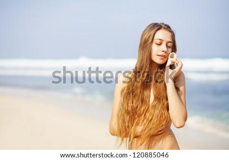 Pretty female with sea shell on beach, bali - stock photo