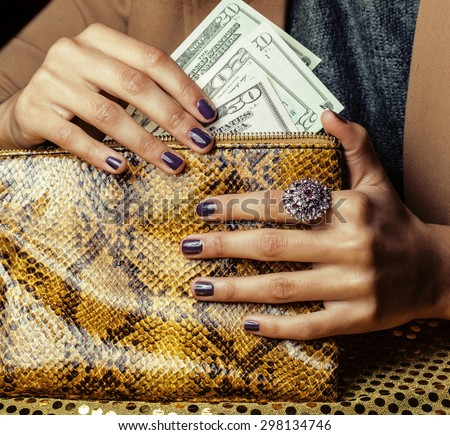 pretty fingers of african american woman holding money close up with purse, luxury jewellery on python clutch, cash for gifts manicure - stock photo
