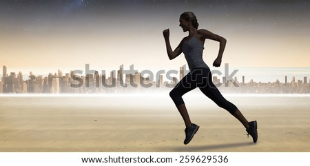 Pretty fit blonde jogging against sun shining over city - stock photo