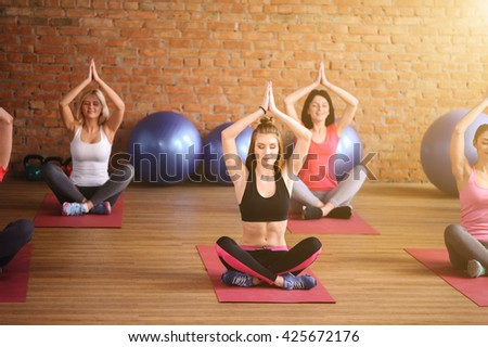 Pretty fit girls are meditating in gym - stock photo