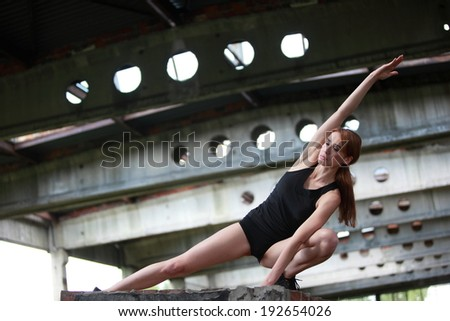 Pretty fit woman exercising in black gymnastic outfit in postindustrial environment - stock photo