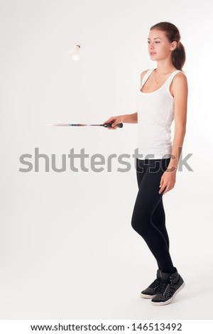 Pretty fit woman holding badminton racket at white background - stock photo