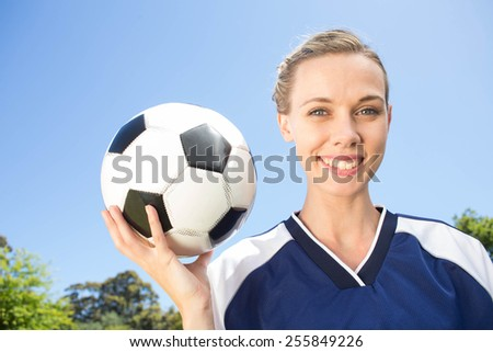Pretty football player smiling at camera on a sunny day