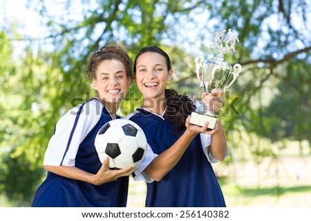 Pretty football players cheering at camera on a sunny day - stock photo