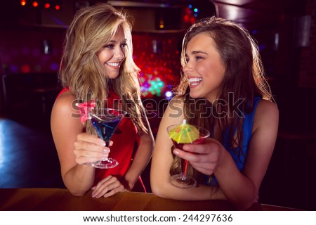 Pretty friends drinking cocktails together at the nightclub - stock photo