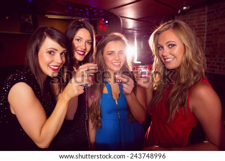 Pretty friends drinking shots together at the nightclub - stock photo